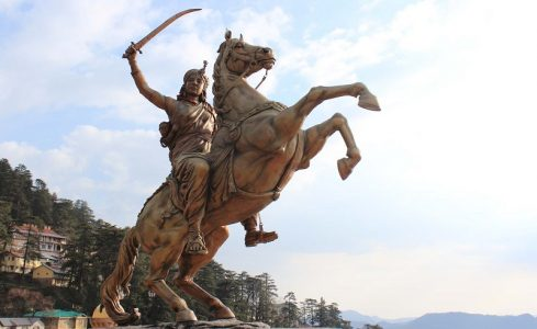 Sculpture of Rani Lakshmi Bai, fighting his enemies with his adopted son at back.