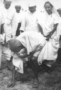 Gandhiji at Dandi picking up salt in a protest against British Government.