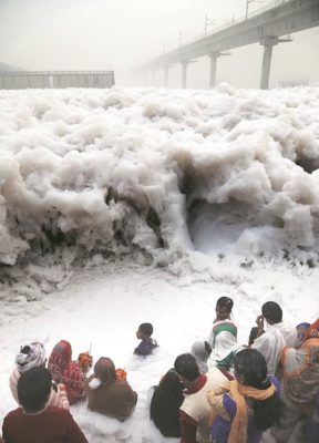 People Celebrating Phhath Puja in the dirty water of Yamuna River. The same river later Joins Ganges in Allahabad. Image Source: The Indian Express
