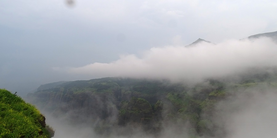 View of The Western Ghats from Top of Tamhini Ghat. The lush green ghats with foggy weather is an ideal place for travellers.